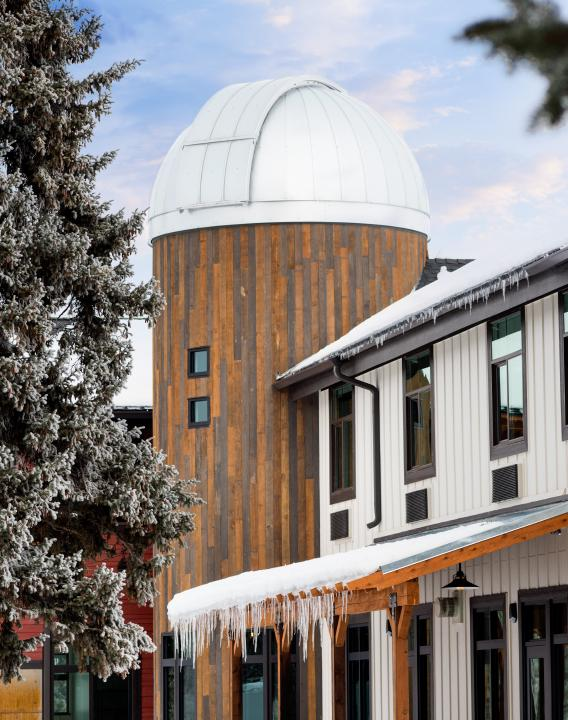 Outdoor side view of the HALO Observatory and the Compass Rose Lodge with snow on the building.