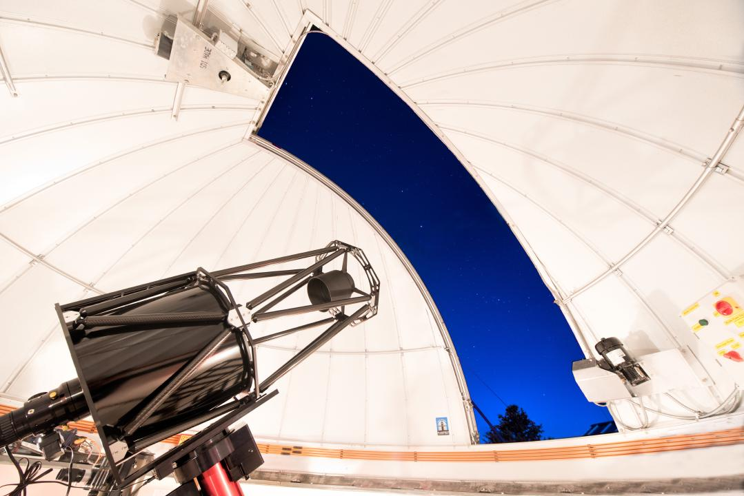The telescope inside of the HALO Observatory with bright lights lighting up the inside of the Ash-Dome.
