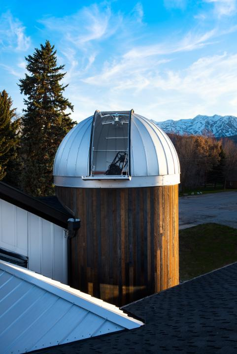 Outdoor view looking at the HALO Observatory during the day with the Ash-Dome door open