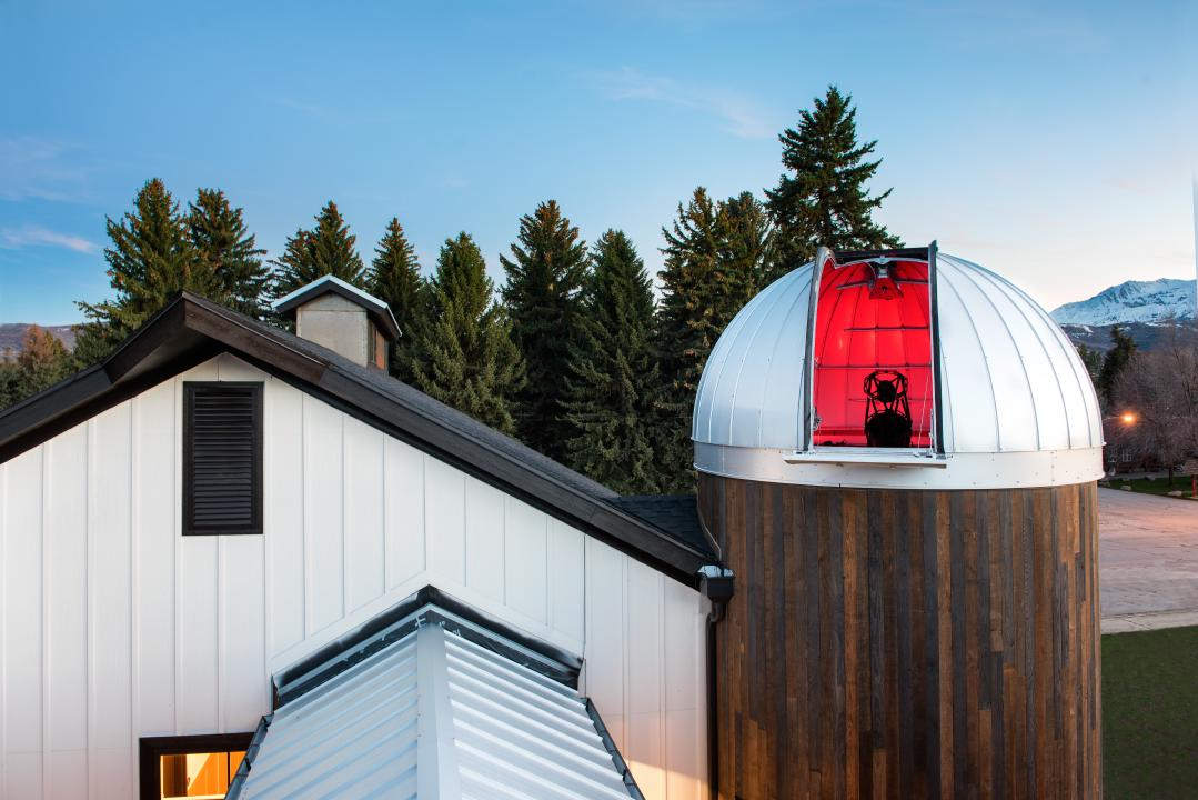 Outdoor view looking at the HALO Observatory with a red light on inside the Ash-Dome with the door open