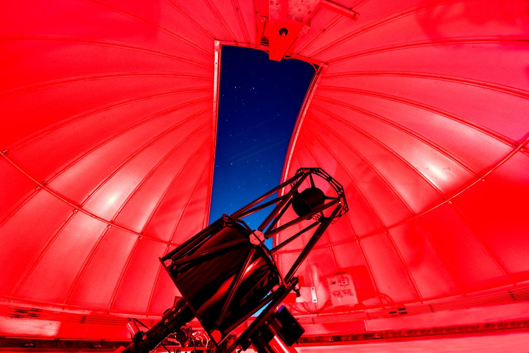 Indoor view of the HALO Observatory telescope with the Ash-Dome door open looking at the night sky.