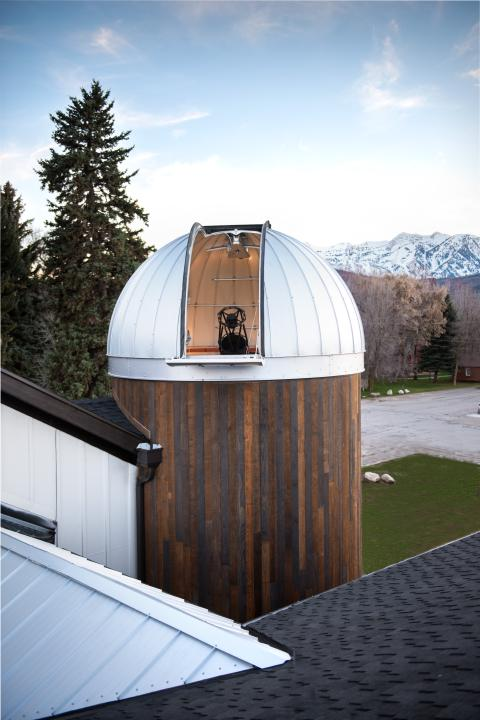 Outdoor view during the day looking at the HALO Observatory with the Ash-Dome door open and the telescope in view.