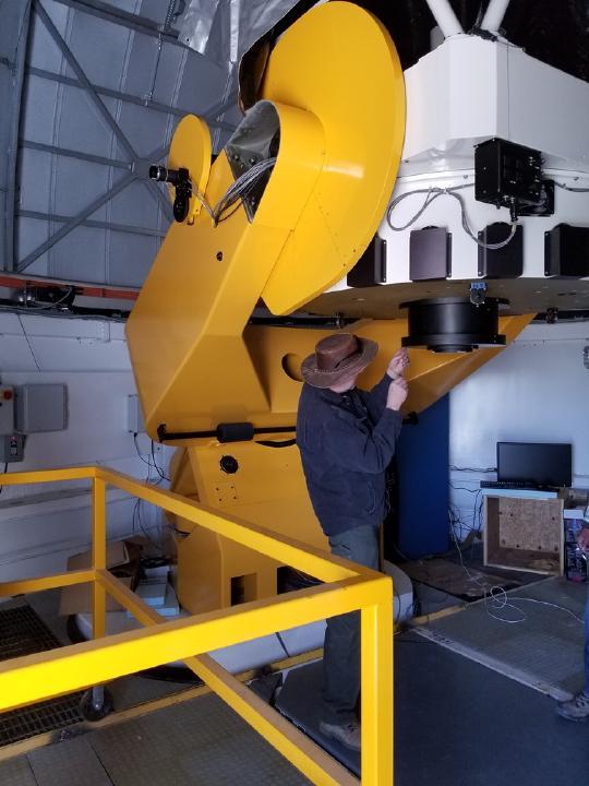 Man working on the telescop inside of TAOS-II