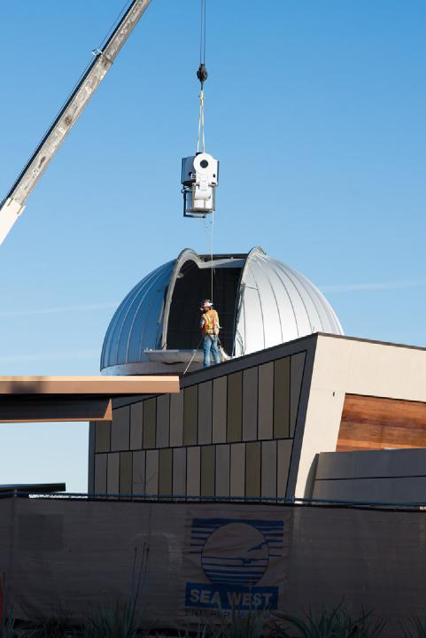 The telescope being lowered into the Rancho Mirage Observatory by a crane.
